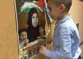 Ahmad Dawabsha looks at poster of his mom (image from family)