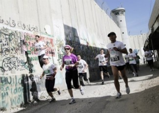 Runners take part in the 2015 Palestine Marathon, skirting Israel's separation wall to the north of Bethlehem. (Right to Movement/Signe Vest)