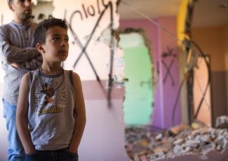 Child stands in home demolished by Israeli army (image by vozisneias.com)
