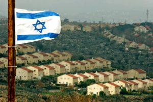Israeli flag flutters over view of Jewish settlement of Ofra...An Israeli flag flutters over the view of the West Bank Jewish settlement of Ofra near the unauthorized outpost of Amona January 12, 2006. REUTERS/Laszlo Balogh