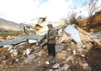 Palestinian man next to his demolished home this week (PCHR photo)