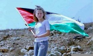 Ahed holding the Palestinian flag at a protest
