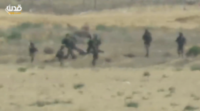 Soldiers drag Palestinian after shooting him (image from Al Quds video)