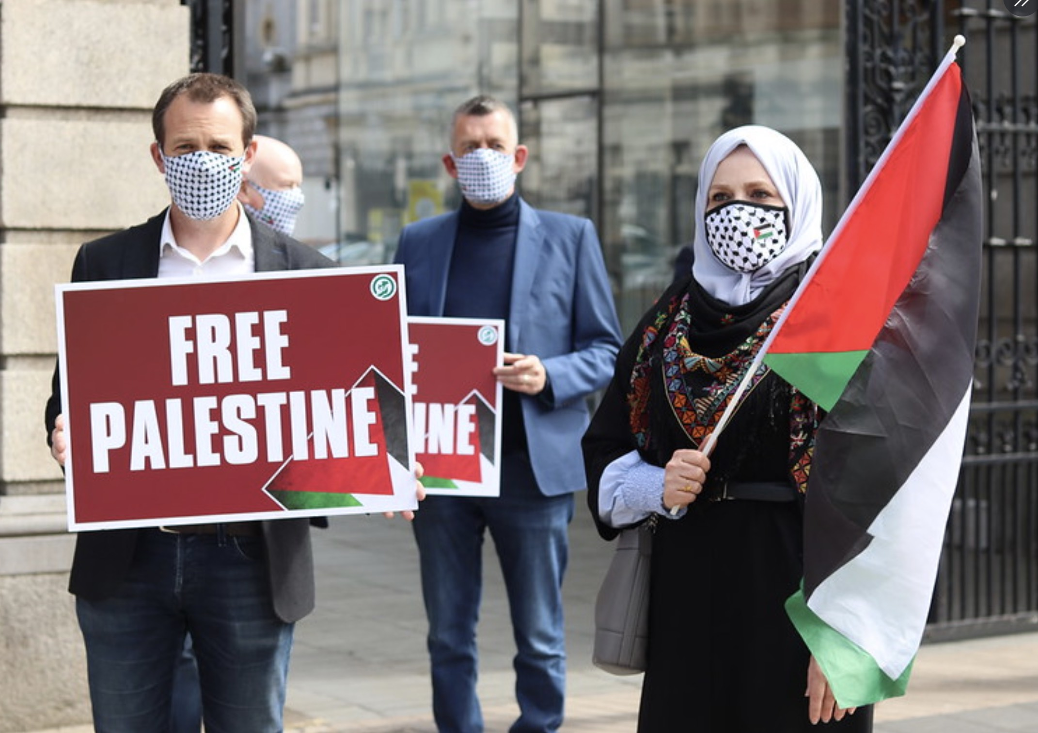 """People hold palestinian flags and """"free Palestine"""" signs Irish government shows solidarity with Palestinians in a historic motion to condemn Israeli settlement activity as defect annexation. photo credited to @sinnfeinireland"""
